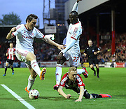 Alex Pritchard getting double teamed and fouled during the Sky Bet Championship first leg play off match between Brentford and Middlesbrough at Griffin Park, London, England on 8 May 2015. Photo by Matthew Redman.