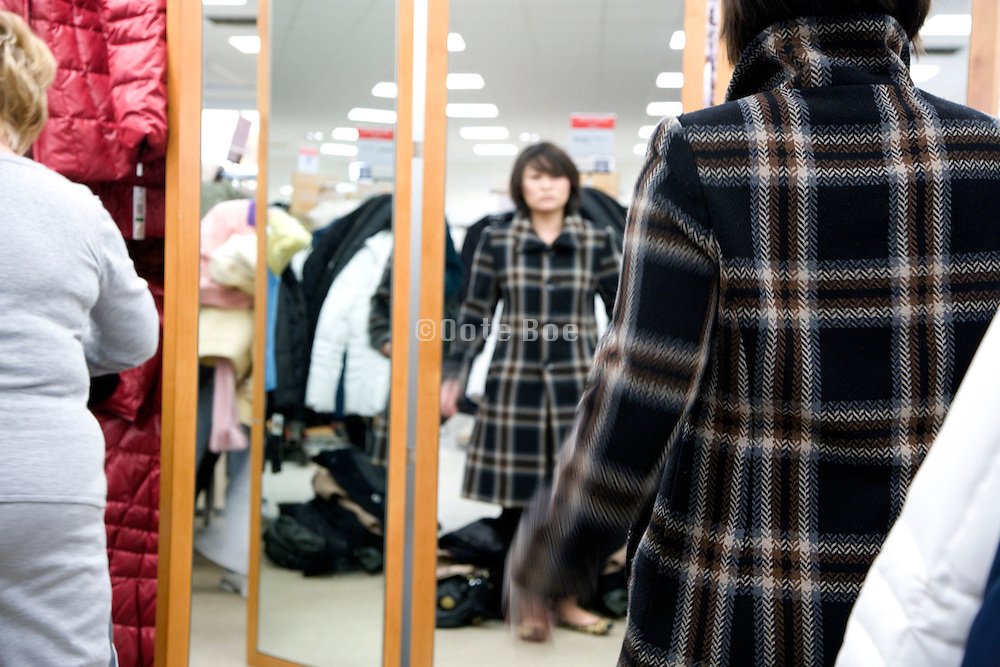 young Asian woman shopping for a new winter coat during the after Christmas discount sale