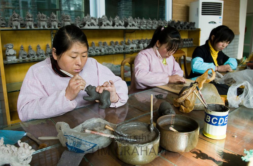 Women make clay figure souvenirs in factory, Xian, China