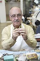 Skilled mature man repairing watch in workshop