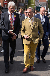 © Licensed to London News Pictures . 24/04/2014 . Knutsford , UK . UKIP leader NIGEL FARAGE wearing yellow cord trousers and jacket on a walkabout tour of Knutsford on the European election campaign trail with former UKIP Wythenshawe and Sale East candidate John Bickley (l) . Farage has come under fire in recent days over a controversial UKIP billboard campaign . Photo credit : Joel Goodman/LNP