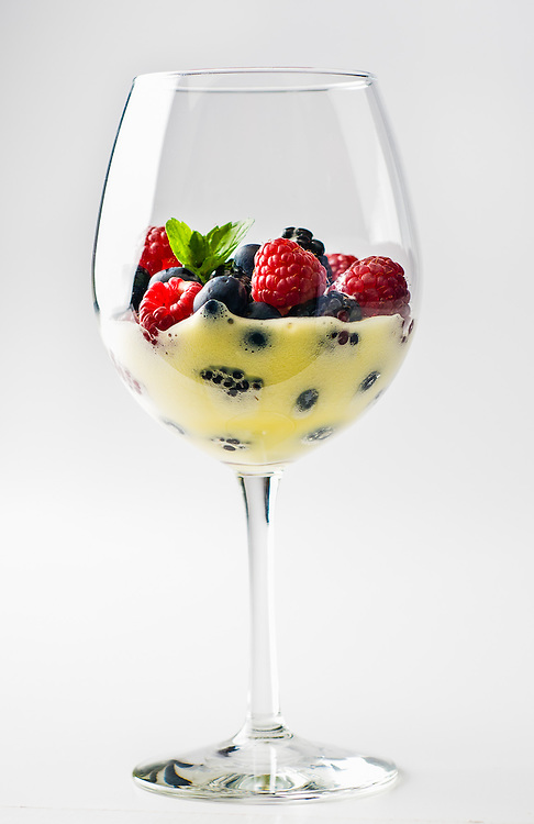 Wine glass filled with berries sabayon dessert. Berries covered in a light champagne custard froth.