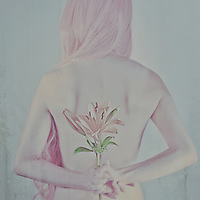 Woman with pink hair holding flowers behind her back.