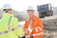 Happy engineer discussing with colleague at construction site on sunny day