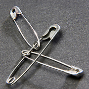 Three safety pins joined together on a gray background