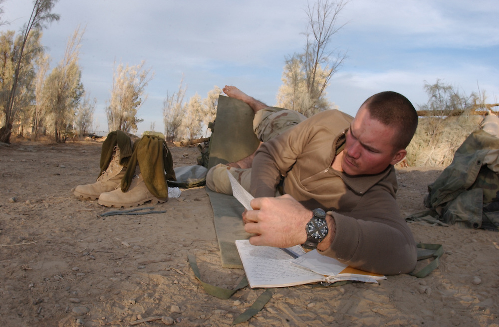 011228-N-2383B-517.KANDAHAR (December 28, 2001) -- At the U.S. Marine Corps Base in Kandahar, Afghanistan, Cpl. Ryan Scheucher of Kirkland, Ohio, takes the time to write and read letters from home.  Cpl. Scheucher of India Company, 26 MEU(SOC) has been in the fields of Kandahar for two weeks now and will spend his night on watch helping defend and maintain security of the base perimeter.  U.S. Marines are in Afghanistan operating in support of Operation Enduring Freedom.  U.S. Navy photo by Chief Photographer's Mate Johnny Bivera, Fleet Combat Camera Atlantic (RELEASED).