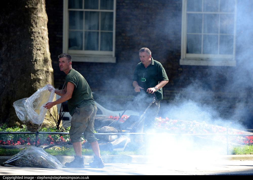 © Licensed to London News Pictures. 30/05/2012. London, UK Garden workers mowing the lawns on Downing Street today, oil burn off from the lawnmower caused a temporary release of smoke across the steet. Preparations today 20th May 2012 around London ahead of The Queen's Diamond Jubilee this weekend. Photo credit : Stephen Simpson/LNP