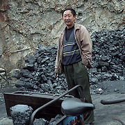 The Coal is ready to be sold on the streets. People employ coal for heating and cooking. Here it is weighted . Individuals often buy it in large amounts and then sold on the streets in carts and on bycicles.