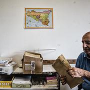 Angelo prende une enveloppe avec les effets personnels d'une des victimes. Il s'agit des victimes identifiés mais dont les familles n'ont pas encore pu récupérer les biens.