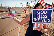 30 MAY 2011 - PHOENIX, AZ: RITA RAFFERTY, from Tempe, AZ, hands out American flag stickers before Memorial Day services in the National Memorial Cemetery in Phoenix, AZ, Monday. Memorial Day was celebrated with services across the United States Monday.    Photo by Jack Kurtz