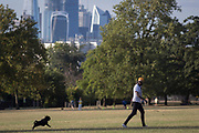 A dog owner looks back towards his pet in Ruskin Park with the skyline of the City of London's financial district, on 8th August 2018, in London, England.
