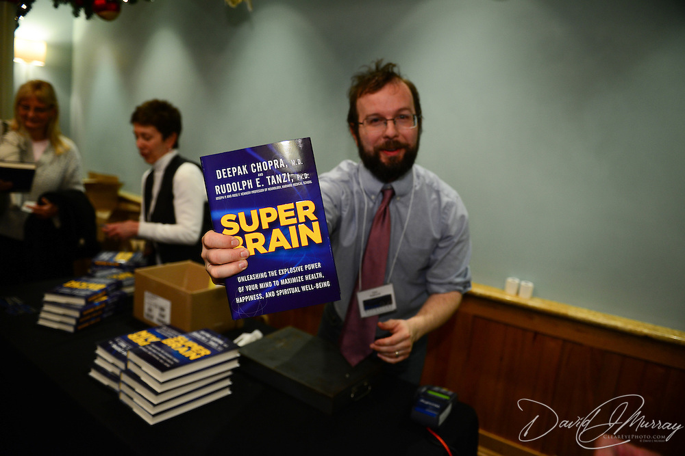 Tom Holbrook of RiverRun Bookstore distributes copies of Super Brain by Deepak Chopra before Chopra speaks at The Music Hall in Portsmouth, NH