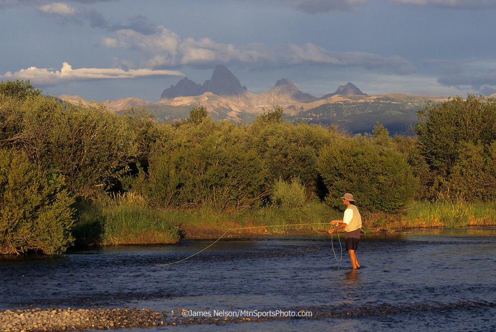 08234-B. An angler fly fishes for trout on east Idaho's Teton River, with the Teton Range of Wyoming in the background.