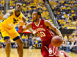 Feb 20, 2016; Morgantown, WV, USA; Oklahoma Sooners guard Jordan Woodard (10) drives baseline past West Virginia Mountaineers forward Elijah Macon (45) during the first half at the WVU Coliseum. Mandatory Credit: Ben Queen-USA TODAY Sports