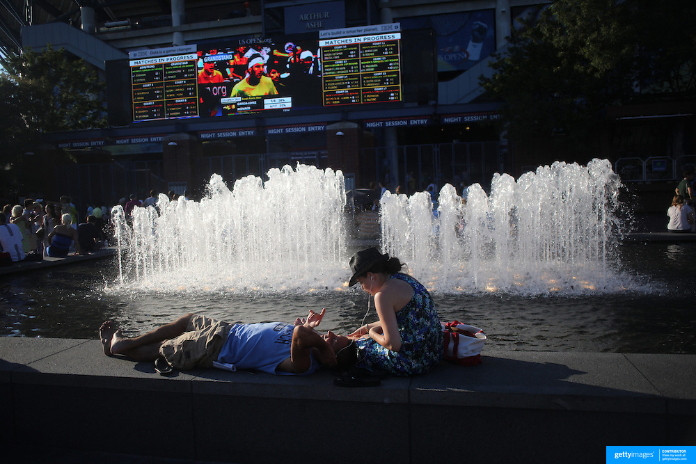 Spectators relax by the water fountain in front of Arthur Ashe stadium during the US Open Tennis Tournament, Flushing, New York. USA. 28th August 2012. Photo Tim Clayton