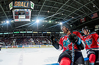 KELOWNA, CANADA - OCTOBER 27: Kole Lind #16 and Carsen Twarynski #18 of the Kelowna Rockets sit on the boards ready to fist bump teammates to celebrate a goal against the Tri-City Americans October 27, 2017 at Prospera Place in Kelowna, British Columbia, Canada.  (Photo by Marissa Baecker/Shoot the Breeze)  *** Local Caption ***
