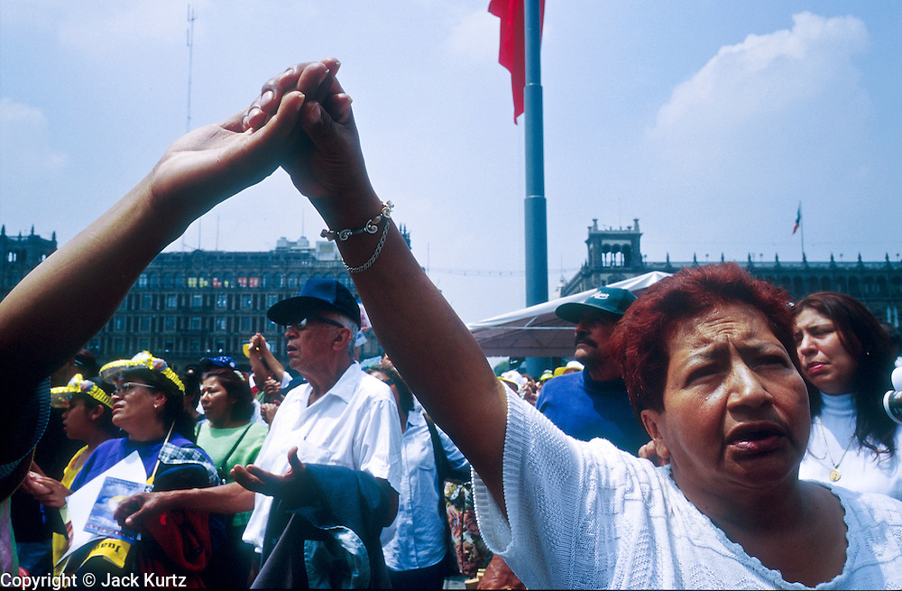 "jku032303054 - 31 JULY 2002 - MEXICO CITY, DF, MEXICO: People pray on the Zocalo in the historic center of Mexico City during a Papal mass televised to the Zocalo on large screen ""jumbotron"" televisions. The mass, led by Pope John Paul II, was at the Basilica of Guadalupe in Mexico City, July 31, 2002. The Pontiff, making his fifth trip to Mexico, canonized Juan Diego, the Mexican Indian who first saw the image of the Virgin of Guadalupe in 1531. Juan Diego is now known at Saint Juan Diego. PHOTO © JACK KURTZ  RELIGION  INDIGENOUS  CULTURE  PATRIOTISM"