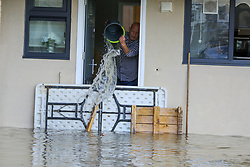© Licensed to London News Pictures. 08/10/2019. London, UK. A resident pours water from his flooded flat, following a burst water main on Brownswood Road in Finsbury Park, north London, causing flooding in a housing estate. Emergency services and Thames Water are at the scene.  Photo credit: Dinendra Haria/LNP