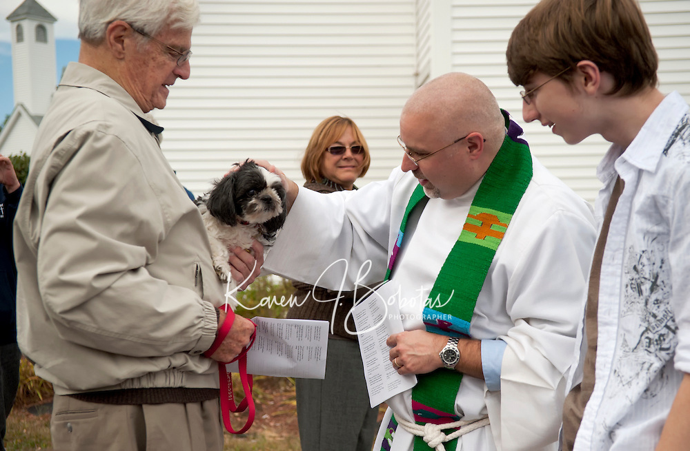 Jerry Kent brought along his dog Morris to the Good Shepherd Lutheran Church Sunday morning to be blessed by Pastor Dave Dalzell during the annual blessing of the animals and soil celebration.  (Karen Bobotas/for the Laconia Daily Sun)