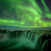 Goðafoss, the Waterfall of the Gods, cascades under the electric glow of an intense aurora borealis.