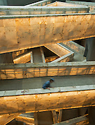 Labourer cleaning alabaster clad ramps, lit from the interior of the Canadian Museum for Human Rights (CMHR)<br /> Winnipeg<br /> Manitoba<br /> Canada