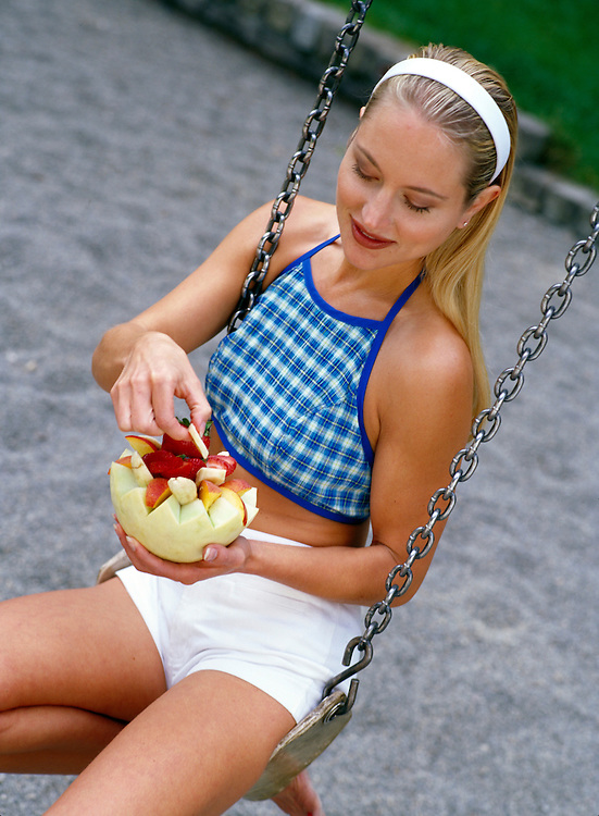 Wellness image of young blond woman sitting on a swing and eating fruit.