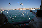 Istanbul. Passengers of a ferry on the Bosporus feeding seagulls. Galata tower and Bridge (l.)