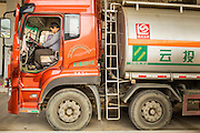 14 MARCH 2013 - ALONG HIGHWAY 13, LAOS: A Chinese truck driver does paperwork in the cab of his truck at the end of Highway 13 in the Boten Special Economic Zone. The SEZ is in Laos immediately south of the Lao Chinese border. It has turned into a Chinese enclave but many of the businesses struggle because their goods are too expensive for local Lao to purchase. Some of the hotels and casinos in the area have been forced to close by the Chinese government after reports of rigged games. The paving of Highway 13 from Vientiane to near the Chinese border has changed the way of life in rural Laos. Villagers near Luang Prabang used to have to take unreliable boats that took three hours round trip to get from the homes to the tourist center of Luang Prabang, now they take a 40 minute round trip bus ride. North of Luang Prabang, paving the highway has been an opportunity for China to use Laos as a transshipping point. Chinese merchandise now goes through Laos to Thailand where it's put on Thai trains and taken to the deep water port east of Bangkok. The Chinese have also expanded their economic empire into Laos. Chinese hotels and businesses are common in northern Laos and in some cities, like Oudomxay, are now up to 40% percent. As the roads are paved, more people move away from their traditional homes in the mountains of Laos and crowd the side of the road living off tourists' and truck drivers.    PHOTO BY JACK KURTZ