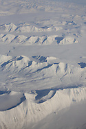 Aerial view in April of mountains and plains covered in snow in the arctic wilderness southern Spitsbergen island; Svalbard, Norway.