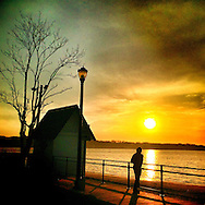 Sea Cliff, New York: April 2015 --  A jogger stops to take in the sunset at . ©Audrey C. Tiernan