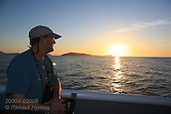 Cruise ship passenger on Lindblad's Sea Lion admires sunrise on Sea of Cortez, Baja California Sur, Mexico