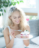 Beautiful woman having raspberry cake with fork in house