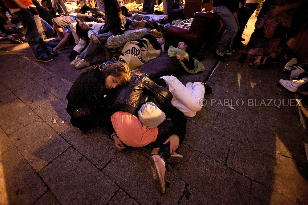 Protesters rest at Puerta del Sol square Camp in Madrid in the early hours on May 21, after all-night festivities in defiance of a 48-hour ban ahead of local elections. Some 25,000 people, according to Spanish media, crammed the central Puerta del Sol square and surrounding streets late on May 20, 2011 to stage a silent protest and then erupted in whistles and cheers of joy as the ban, ordered by Spain's election commission, took effect at midnight.