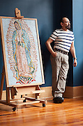 Artist Hector Hernandez stands next to his mosaic of The Virgen de Guadalupe at the Erikson Gallery where his art will be exhibited until June 30th as part of the Saints &amp; Sinners Rose City Art Show. He is working on another mosaic of the  Virgen de Guadalupe similar to this one that will be on permament dispaly at The Grotto. <br /> Image by Shauna Intelisano