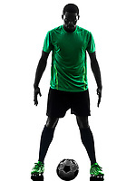 one african man soccer player green jersey standing in silhouette on white background