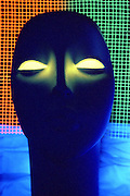 Mannequin with glowing eyes and colorful glowing mesh.Black light
