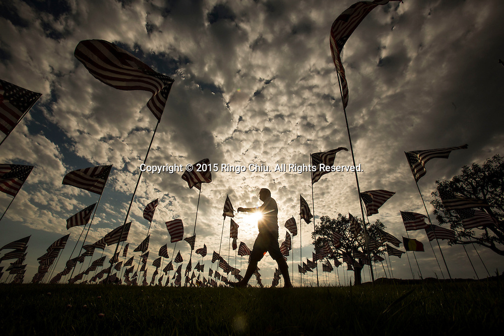 A man walks through amongst 3,000 US flags are displayed at Pepperdine University to mark the 14th anniversary of the 9/11 terror attack, September 10, 2015 in Malibu, California.Photo by Ringo Chiu/PHOTOFORMULA.com)