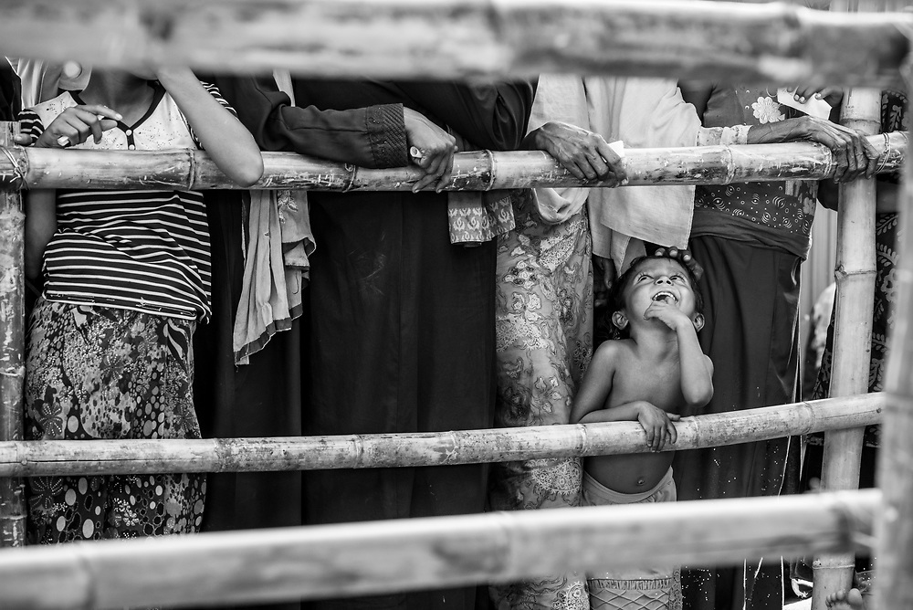Three-year-old Shehena waits in line with her mom and other women for a humanitarian aid distribution in Jamtoli refugee camp, Bangladesh (October 26, 2017)