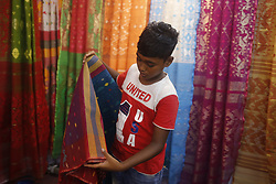 May 26, 2019 - Dhaka, Bangaldesh - A boy folds a Jamdani Sharee as he sale at a fair ahead of Eid-UL-Fite after the holy month of the Muslim of Ramadan in Dhaka. (Credit Image: © MD Mehedi Hasan/ZUMA Wire)