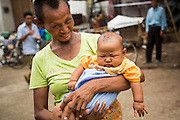 08 JUNE 2014 - YANGON, MYANMAR: A woman and her child on the Yangon waterfront. Yangon, Myanmar (Rangoon, Burma). Yangon, with a population of over five million, continues to be the country's largest city and the most important commercial center.      PHOTO BY JACK KURTZ