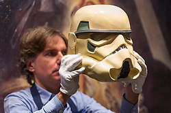"© Licensed to London News Pictures. 06/12/2019. LONDON, UK. A staff member poses with a ""Prototype Imperial Stormtrooper Helmet"", 1976 (Estimate GBP30,000-60,000) in front of a movie poster, at the preview of ""Star Wars Online"", a sale dedicated to Star Wars collectibles encompassing 100 lots from the franchise.  Sotheby's will host the online-only sale which will run until 13 December, ahead of the final film in the sequel trilogy ""Star Wars: The Rise of Skywalker"".  Highlights from the sale are on display at Sotheby's New Bond Street 6 to 11 December.  Photo credit: Stephen Chung/LNP"