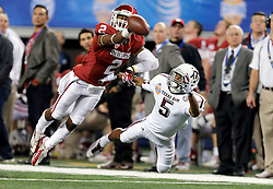 Texas A&M Aggies wide receiver Kenric McNeal (5) and Oklahoma Sooners defensive back Julian Wilson (2) layout for a ball during the 77th AT&T Cotton Bowl Classic between the Texas A&M University Aggies and the Oklahoma University Sooners at Cowboys Stadium in Arlington, Texas. Texas A&M wins the 77th AT&T Cotton Bowl Classic against Oklahoma, 41-13.
