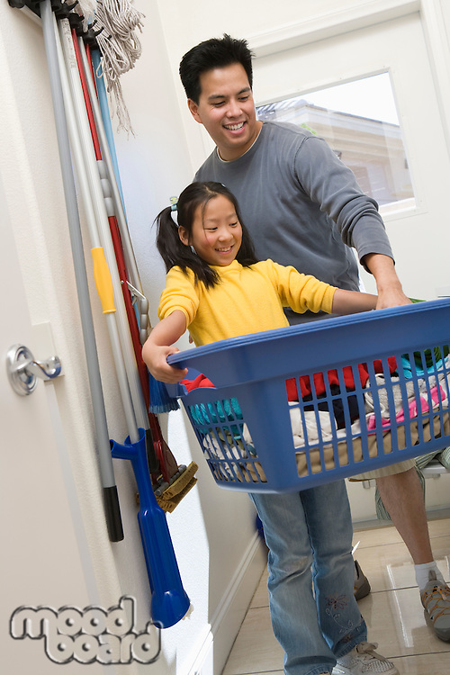 Girl carrying laundry basket, her father assisting her