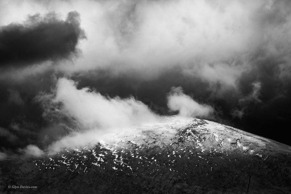 Although I stood in brilliant sunshine on my mountain top, clouds billowed over the main Snowdonia peaks, set against an ominous dark sky. Sunlight punched through the swirling vapour illuminating patches of hillside and ocassionally the summits themselves