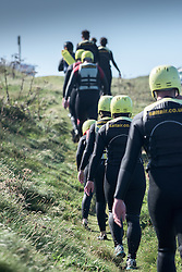 Holidaymakers walking back to their base after finishing a Coasteering session on The Headland in Newquay, Cornwall.
