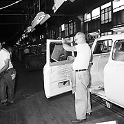 A Studebaker worker installs door window glass on a 1960 Studebaker Lark station wagon body.