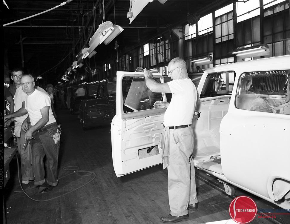 A Studebaker worker installs door window glass on a 1960 Studebaker Lark station wagon body.