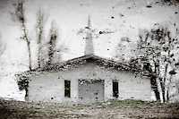 reflection of old country church in puddle of water after a rain in rural Southern America