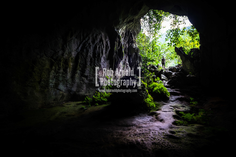 A man stands and looks in through the entrance to Tham Kang Cave near Nong Khiaw in Laos
