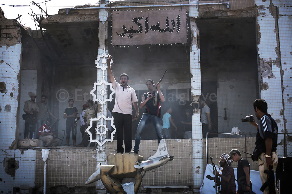 Libyan rebels  celebrate the day after they stormed Bab Al Azizyia,  Gadhafi headquarters compound in Tripoli. 24 August 2011.